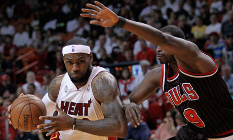 Miami Heat's James drives against Chicago Bulls' Deng in first half NBA game in Miami