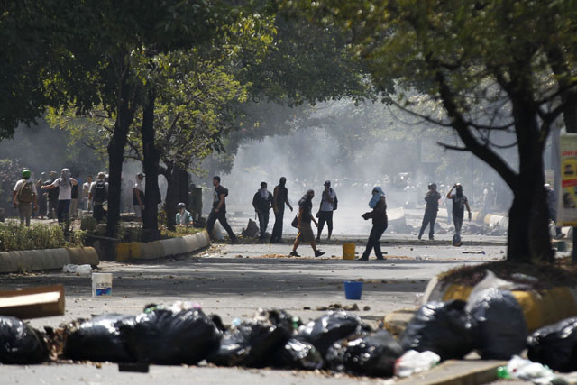 Anti-government protesters clash with the national police during riots in Caracas