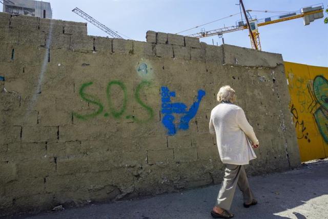 """Un hombre camina junto a un muro donde aparece un grafiti pidiendo la liberación del dirigente político venezolano opositor Leopoldo López hoy, jueves 5 de junio del 2014, en el municipio de Chacao, en Caracas. La defensa de López dijo hoy que el juicio que afrontará por su presunta responsabilidad en los incidentes violentos del 12 de febrero pasado puede iniciarse a fines de agosto y aseguró que este será un proceso al que acudirán """"amarrados"""", sin pruebas. EFE/SANTI DONAIRE"""