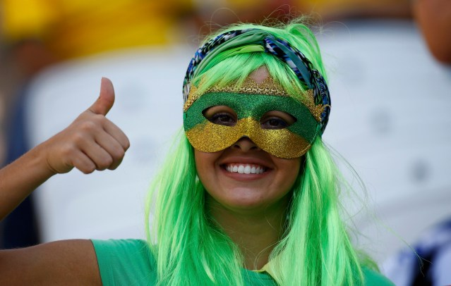 A fan gestures before the opening ceremony of the 2014 World Cup at the Corinthians arena in Sao Paulo