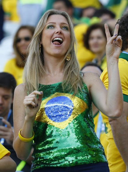 A fan poses before the opening ceremony of the 2014 World Cup at the Corinthians arena in Sao Paulo