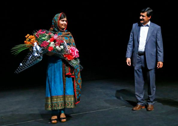 Pakistani schoolgirl Malala Yousafzai, the joint winner of the Nobel Peace Prize, stands with her father Ziauddin after speaking at Birmingham library in Birmingham