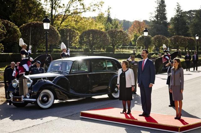 Los reyes de España y la presidenta de Chile, Michelle Bachelet (d), durante la interpretación de los himnos de los dos países, en el recibimiento oficial en los exteriores del Palacio de El Pardo, donde inicia una visita de Estado centrada en la promoción de proyectos de cooperación económica. EFE/ EMILIO NARANJO