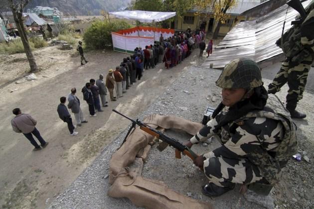 Un soldado vigila mientras varios votantes guardan su turno ante un colegio electoral para participar en la jornada inaugural de las elecciones de la Cachemira india en Bhadarwah, a unos 210 kilómetros de Jammu, la capital de invierno de Cachemira. Muchos votantes desafiaron el frío e hicieron cola antes de la apertura de 1.900 colegios para elegir a 15 de los 87 diputados de la Asamblea regional en un proceso de un mes de duración. EFE/Jaipal Singh