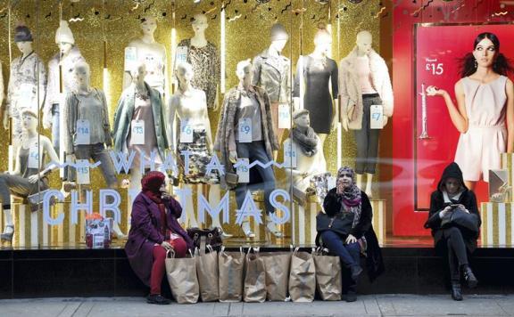 Varias personas con bolsas frente a un escaparate de Oxford Street, durante el inicio de la temporada navideña en Londres, Reino Unido,