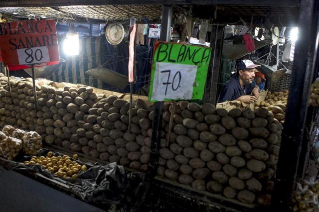 """Un comerciante ofrece papa para la venta en un mercado popular hoy, miércoles 5 de noviembre de 2014, en Caracas (Venezuela). En Venezuela, una familia promedio debe peregrinar por """"el menor costo posible"""" para completar una canasta alimentaria que, aún subvencionada, está un 17 por ciento por encima del salario mínimo y que es irreal con un mercado que ignora las regulaciones del Estado. EFE/Miguel Gutiérrez"""