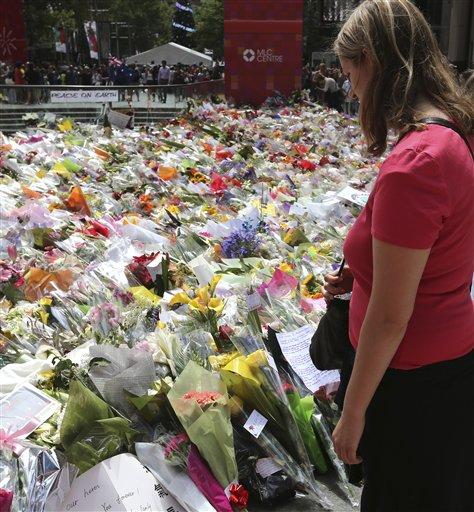 Foto: Una mujer se para para leer mensajes de recuerdo en el punto de homenaje a las víctimas de un asedio mortal, cerca del Lindt cafe donde tuvo lugar, en el distrito financiero de Sídney, Australia, el 18 de diciembre de 2014. AP / Rob Griffith