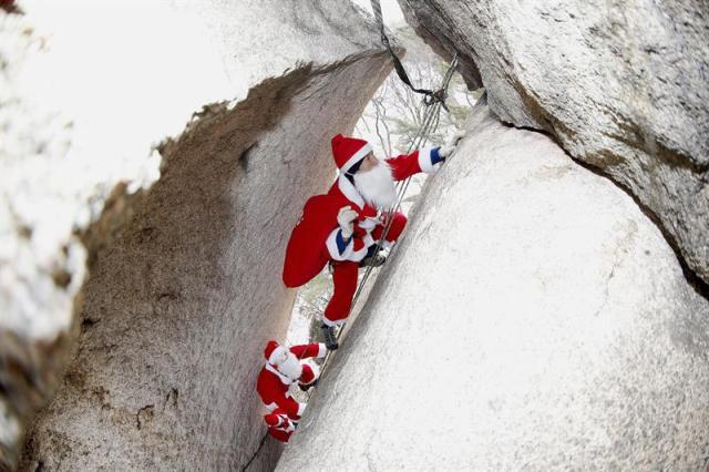 Policía de Corea del Sur en la Montaña Kim Chang- Gon (arriba),  vistiendo trajes de Santa Claus , en una escalada durante un evento que marca la temporada de vacaciones de Navidad en montaña Buckhan cerca de Seúl. EFE/EPA/JEON HEON-KYUN