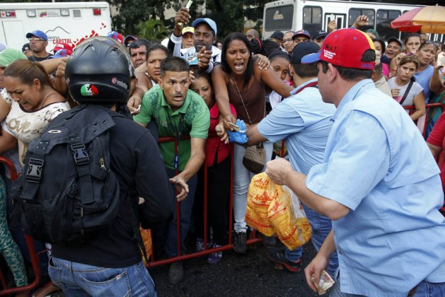 People attempt to buy chickens at a Mega-Mercal, a subsidized state-run street market, in Caracas