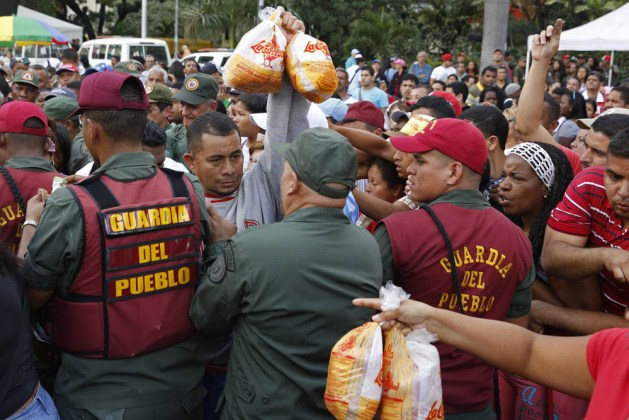 Venezuelan soldiers try to control the crowd as people attempt to buy chickens at a Mega-Mercal, a subsidized state-run street market, in Caracas
