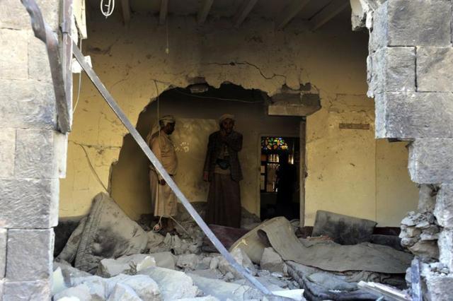 Miembros de la milicia chií de los hutíes inspeccionan el agujero en el muro provocado por la explosión de un artefacto en la sede del grupo en Saná (Yemen) hoy, lunes 5 de enero de 2015, un día después de que al menos seis miembros de este movimiento murieran y otros 31 resultaran heridos al explotar un artefacto en una sede del grupo en la ciudad meridional yemení de Zemar. EFE/Yahya Arhab