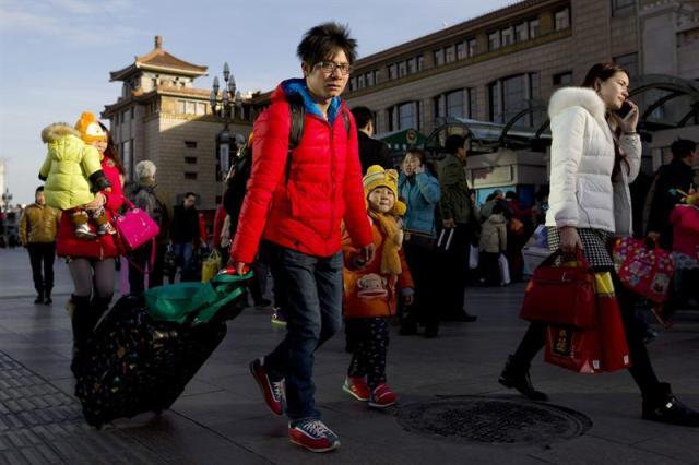 """Numerosas personas llegan a la estación de trenes de Pekín, en China, hoy, 4 de febrero de 2015. China inició hoy el gran """"éxodo"""" festivo por la celebración del Año Nuevo lunar, que se espera que este año conlleve, según las autoridades, unos 2.800 millones de desplazamientos, la mayor movilización poblacional del mundo. La campaña del también llamado Festival de Primavera, principal fiesta del país, llevará de vuelta a casa a millones de chinos que viven lejos de sus hogares, para despedir el año del caballo y comenzar el de la cabra junto a sus familiares y amigos.  EFE/WU HONG"""