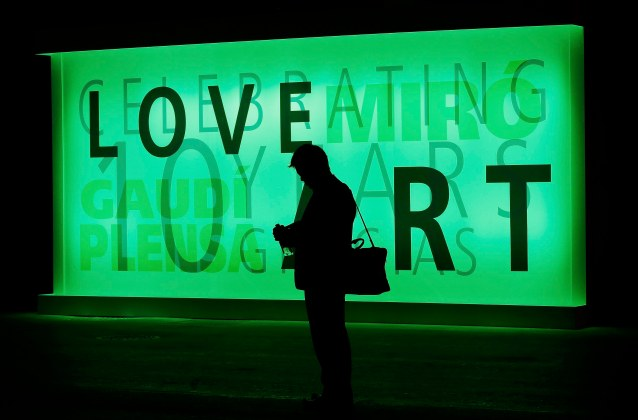 A man checks his mobile phone in front of an illuminated billboard at the Mobile World Congress in Barcelona