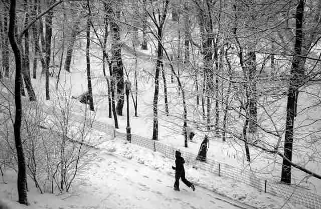 A man jogs in falling snow in Riverside Park in upper Manhattan in New York City in the early morning Thursday