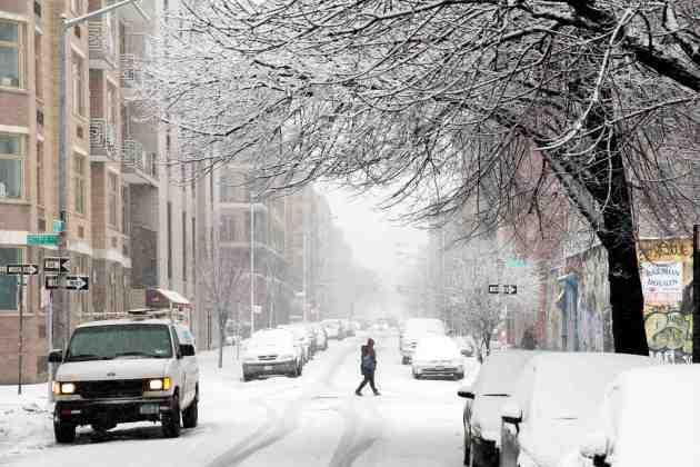 A pedestrian walks through a snow storm in New York