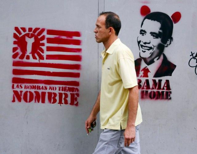 A man walks past graffiti depicting U.S. President Barack Obama in Caracas