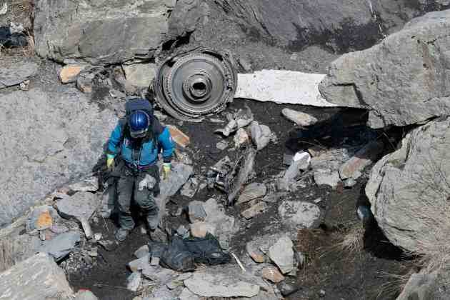A French rescue worker inspects the debris from the Germanwings Airbus A320 at the site of the crash, near Seyne-les-Alpes, French Alps