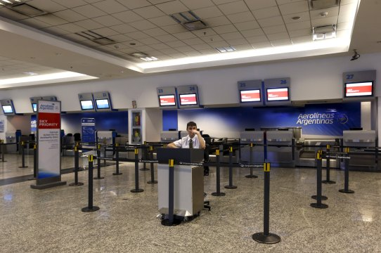 A private security man sits near the check-in desks of Aerolineas Argentinas at the Jorge Newbery domestic airport during a one-day nationwide strike in Buenos Aires