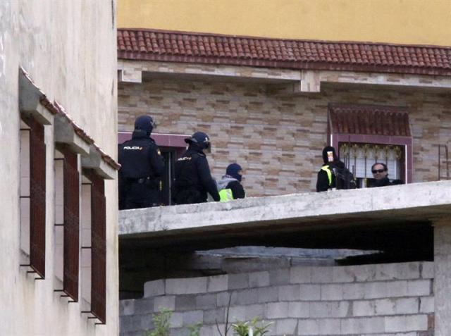 """Efectivos de la Policía Nacional, durante la operación llevada a cabo desde la madrugada en Ceuta contra el terrorismo islamista y en la que han sido detenidas dos personas Desde las cuatro de esta madrugada los agentes de la Comisaría General de Información de la Policía Nacional desplazados desde Madrid han ocupado varias zonas de la barriada acompañados por agentes de la Jefatura de la Policía Nacional de Ceuta.El operativo se centraliza en varias viviendas de este núcleo de población, situado junto a la frontera con Marruecos y que ya ha sido escenario de anteriores operaciones de estas características.Estos dos presuntos yihadistas, según una nota de Interior, """"formaban parte de una célula plenamente preparada y dispuesta para atentar en el territorio nacional"""". EFE/Reduan"""