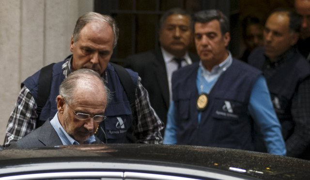 Rato, former People's Party minister and former managing director of the International Monetary Fund, enters a police's car as they leave his residence after an inspection in Madrid