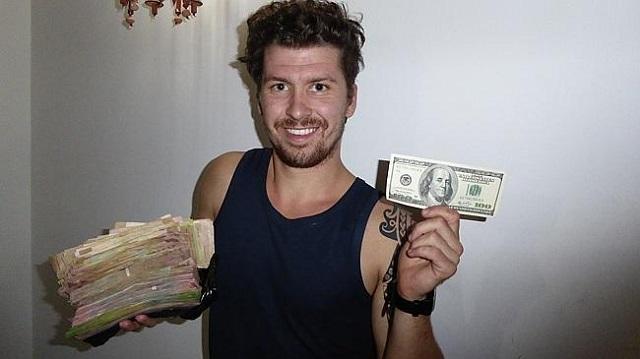 """El mochilero Will Hatton con una """"paca"""" de bolívares en efectivo / Foto Will Hatton"""