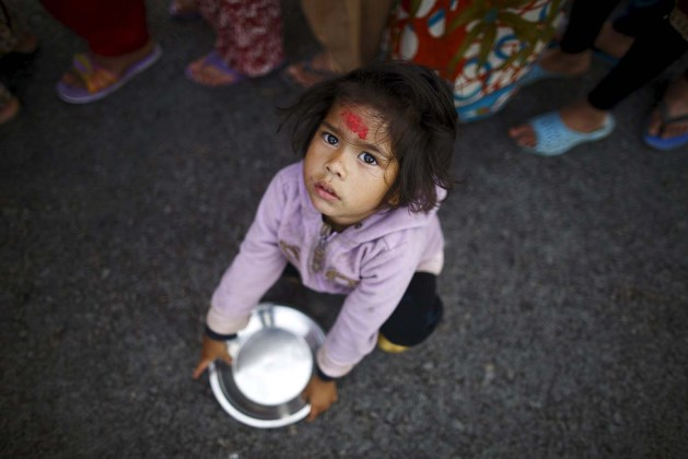 Girl holding her plate sits near the queue to receive food, near a makeshift shelter after the April 25 earthquake in Kathmandu