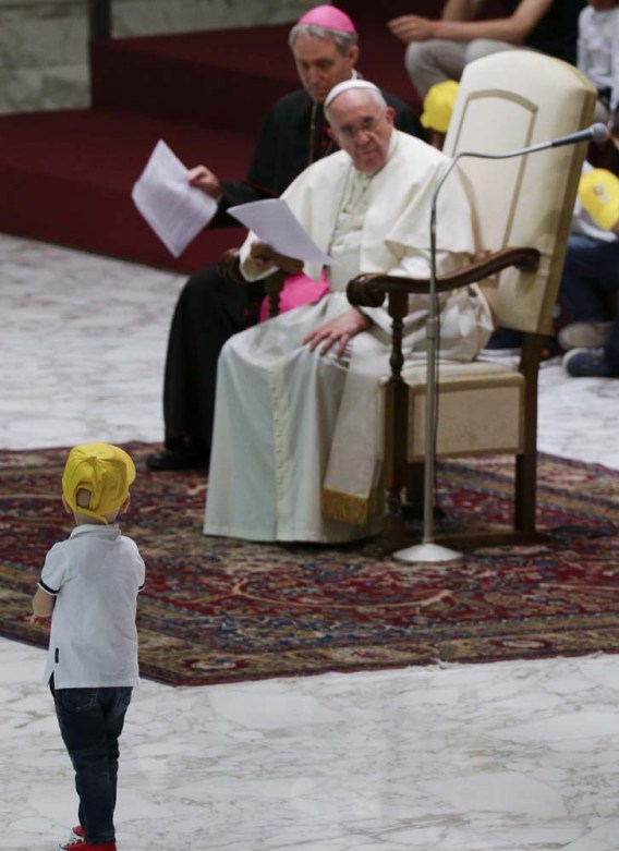 "A boy from the ""Fabbrica della Pace"" group approaches Pope Francis as he holds an audience at the Vatican"