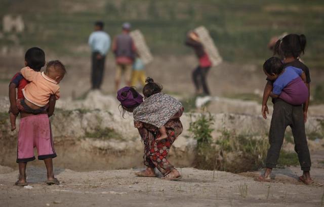 Tres niños se hacen cargo de tres bebés mientras sus madres trabajan en una fábrica de ladrillos en Bhaktapur (Nepal) hoy, martes 19 de mayo de 2015. Nepal ataraviesa una grave crisis del ladrillo tras el terremoto que derribó unos 40 millones de hogares y cerca del 80% de los hornos de ladrillos el 25 de abril de 2015 y durante la réplica del pasado 12 de mayo. El terremoto del día 25 causó en Nepal 8.604 muertos y 16.808 heridos, según el último balance ofrecido por el Ministerio de Interior nepalí, que situó en 488.789 el número de viviendas completamente destruidas por el seísmo y en 761 los edificios gubernamentales. EFE/Narendra Shrestha