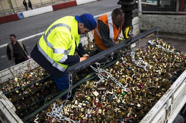 Varios empleados retiran las rejas con los candados que cuelgan del del Pont des Arts de París, Francia, hoy, 2 de junio de 2015. París se despidió ayer para siempre de los miles de candados que colgaban de forma anárquica de las barandillas del Pont des Arts, símbolo del amor para unos y del vandalismo para otros. Bajo la mirada curiosa de varias decenas de turistas decepcionados por no poder acceder al puente, los obreros de la ciudad de París empezaron a cortar a golpe de sierra eléctrica los 37 paneles que protegen las barandillas. El puente estará cerrado al público por motivos de seguridad durante toda esta semana, tiempo que los obreros aprovecharán para acabar de quitar el resto de candados y colocar unos nuevos paneles artísticos, que ocuparán el puente hasta otoño. EFE/ETIENNE LAURENT