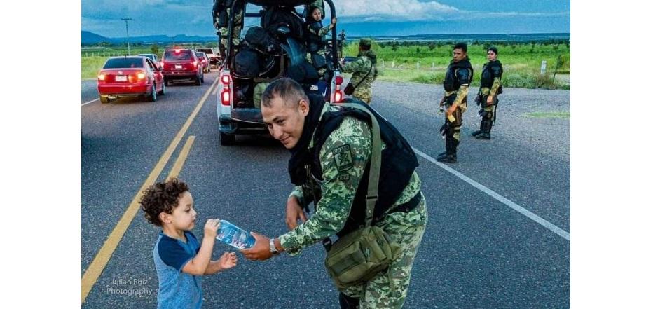 Viralizan foto de niño dándole agua a uno de la guardia