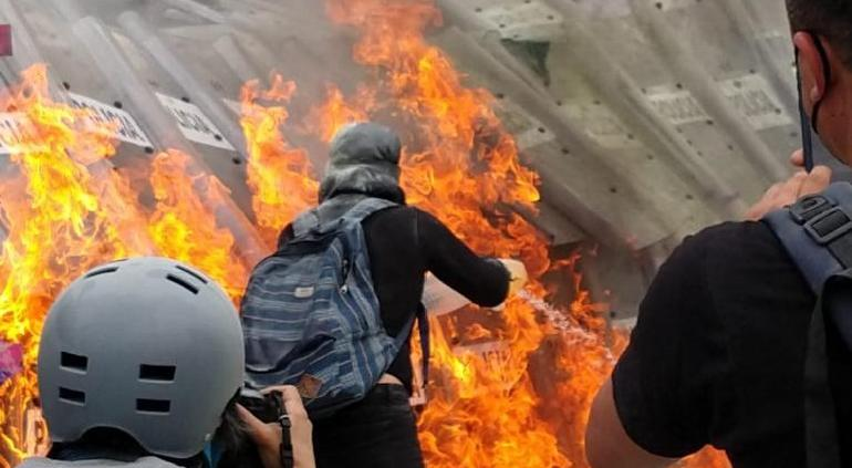 Manifestantes rocían gasolina e incendian a policías en CDMX