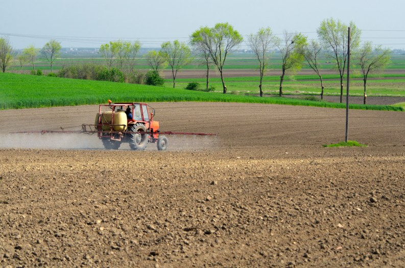 Tractor sprinkling pesticides againt bugs on plowed land on sunny spring day.