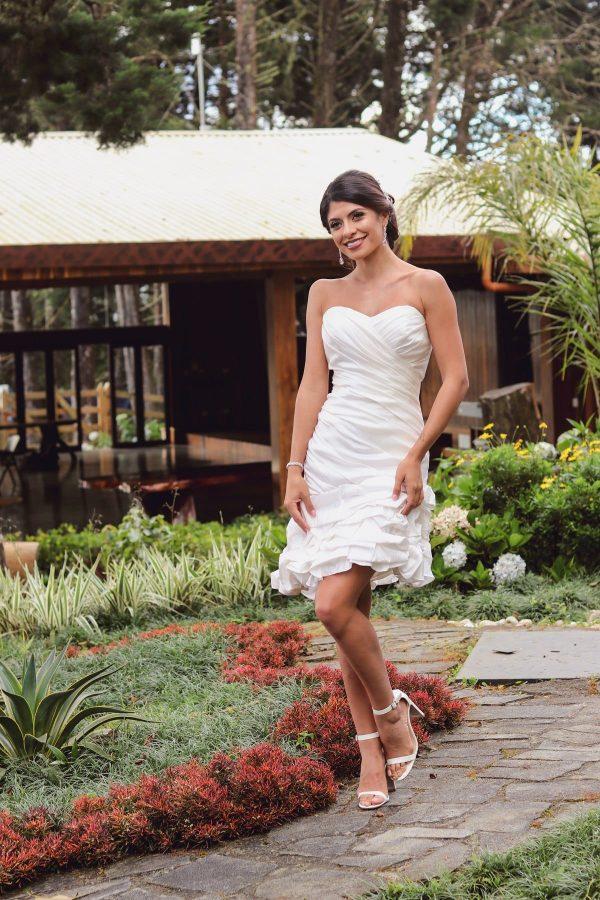Chica en vestido de blanco corto cruzando la pierna