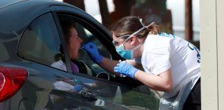 Profesional de la salud hace una prueba de covid-19 a una mujer en un estacionamiento de vehículos, Chessington (Reino Unido), el 15 de abril de 2020. Andrew Couldridge / Reuters