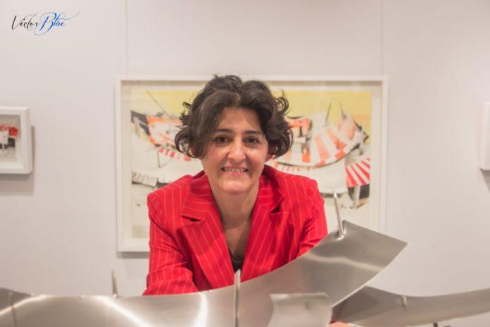 La artista Carmen Márquez Prieto en la Galería Haurie detrás de una de sus esculturas en acero y delante de uno de sus cuadros.