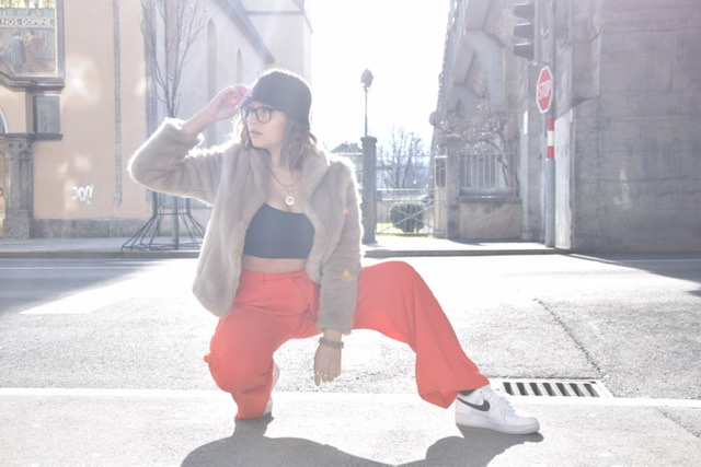 Blogger La Sara Leona is posing in the urban area of Innsbruck with black croptop, red flare trousers, white sneakers from Nike, fake fur coat and fisher hat to style a 90s look.