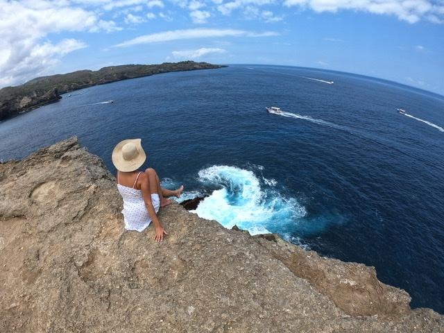 La Sara Leona an der Klippe von angel's billabong auf Nusa penida während ihres bali trips mit weißem Sommerkleid und Sonnenhut vor wirbelnder Gischt in Türkis. Magisches Meer!