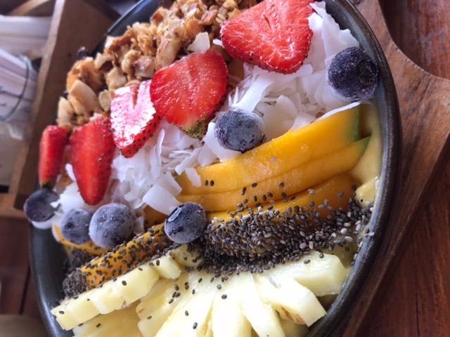 Smoothie Bowl des Bukit Café auf Bali im Süden bei Uluwatu mit Mango, Ananas, Erdbeere, geeisten Blaubeeren und Granola.