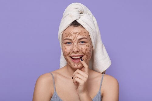 Smiling girl applying coffee mask or scrub on skin, looks at camera, wearing towel, doing beauty treatment manipulation, keeping finger on lips, posing against lilac wall.