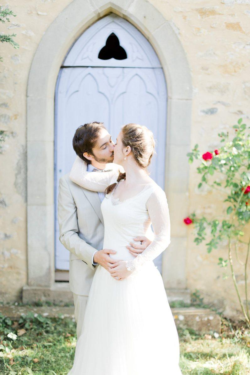 Couple de mariés s'embrassant devant une chapelle