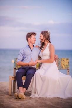 Couple de mariés sur un banc à la plage