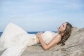 Mariée allongée sur du bois flotté