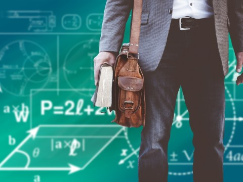 Male Teacher walking with bookbag & book in hand in front of equations