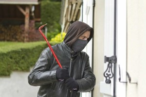 Burglar Gaining Unlawful Access to a Residential Home with a Crowbar
