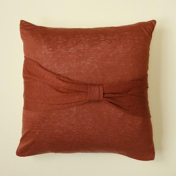 Voici la housse de coussin Bowy, en jersey de lin roux avec un noeud en maille et lin chambray beige.