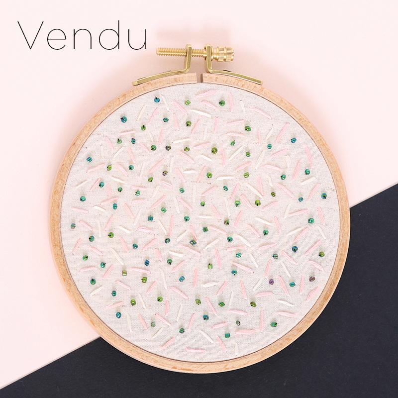 Cadre décoratif Luna, broderie réalisée à la main, en France, sur du tissu upcyclé. Joli motif abstrait aux tons rose pâle, crème et vert sapin.