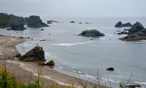 Two rock climbers on the formation nearest the camera have a special view of the Pacific.