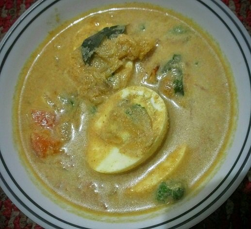 Bowl of Egg curry with coconut.