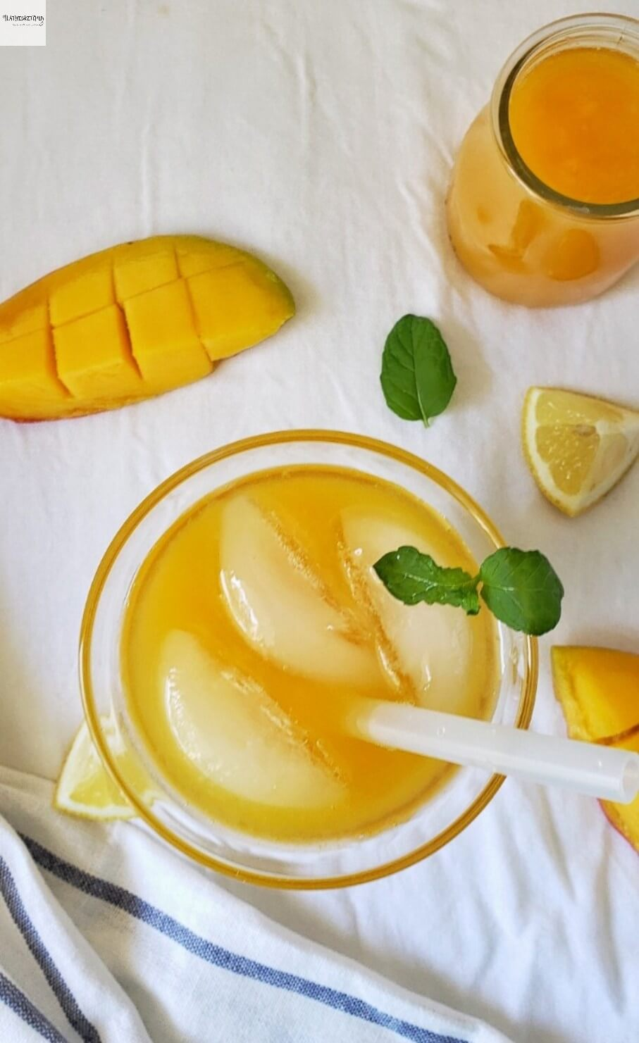 Glass of Mango Lemonade with mango and lemon wedges on side and mint leaves.
