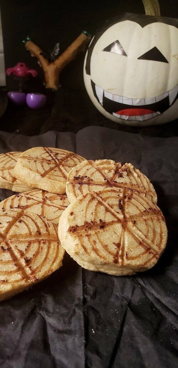 Halloween spider web cookies with pumpkin in the background.